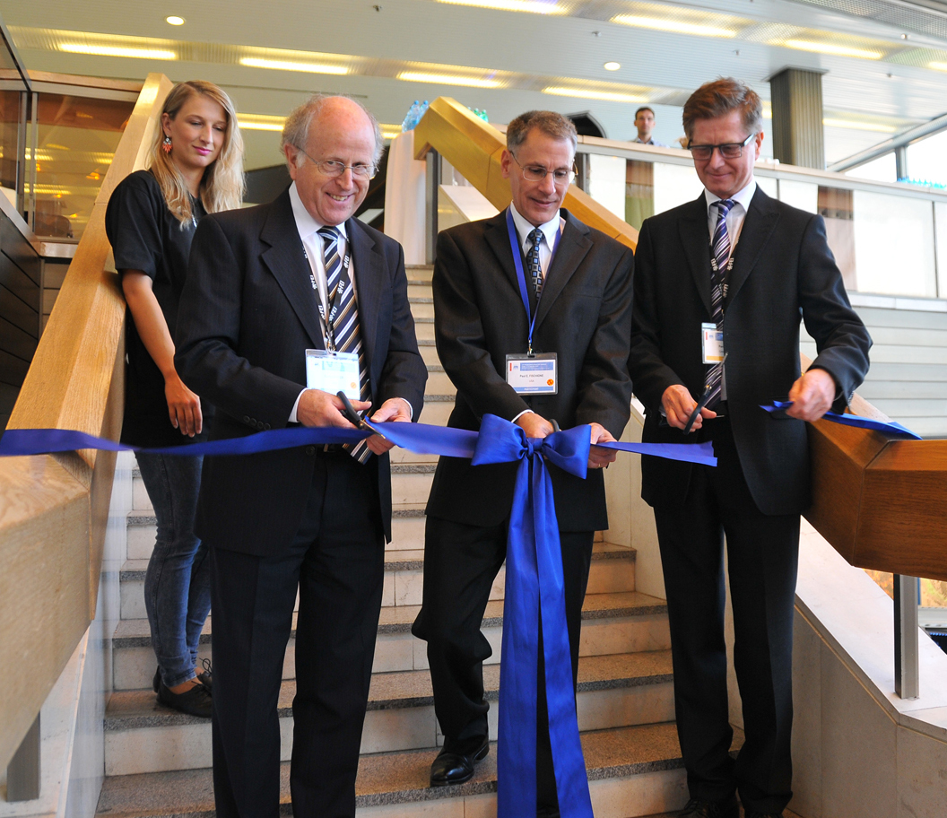 Carter, Fischione, and Hozák cut the ribbon to open the IMC 2014 exhibition